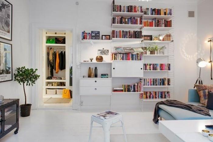 Soggiorno arredato con mobili di colore bianco con mensole a vista e tanti libri