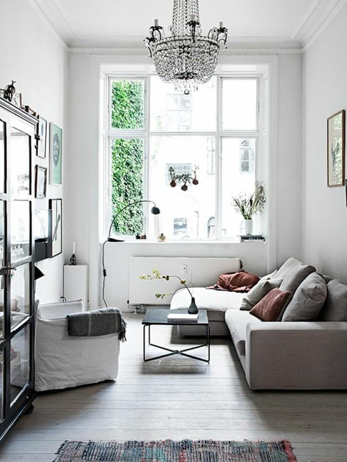 Salotto con un divano angolare di colore grigio e tavolino in ferro battuto di colore nero