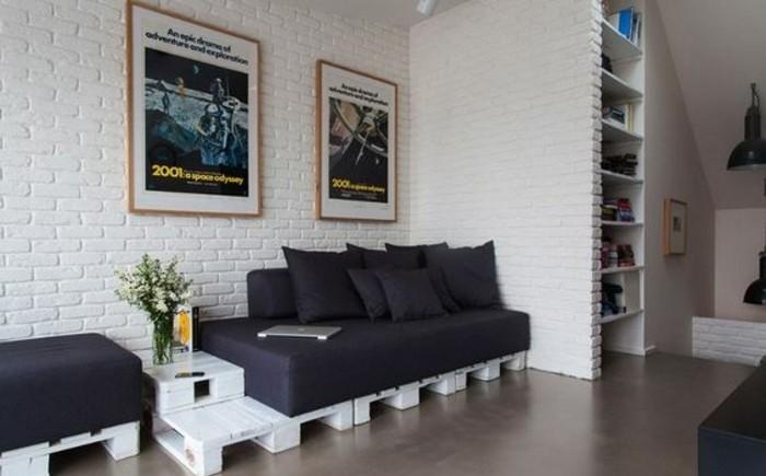 Soggiorno arredato con mobili fai da te in pallet, parete con mattoni in vista e quadri