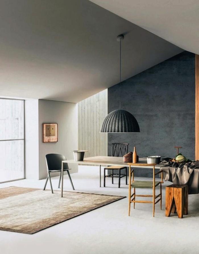 Arredamento con mobili moderni, parete di colore nera abbinata ad un tappeto di colore beige