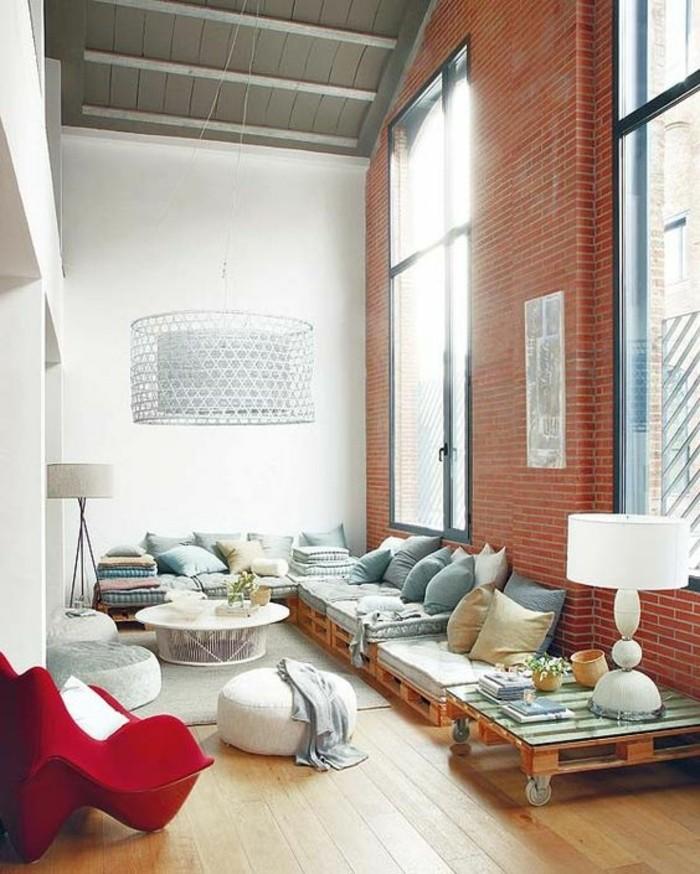 Arredamento con bancali di legno, ambiente in stile industriale, tavolino con superficie di vetro