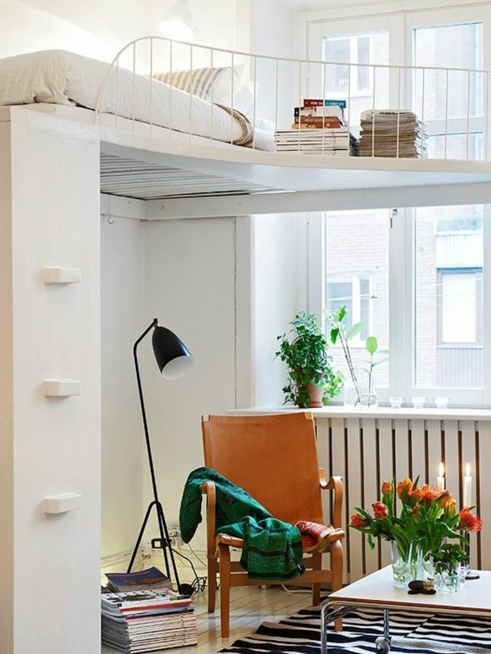Idea arredamento salotto con letto a soppalco di colore bianco e decorazioni con libri