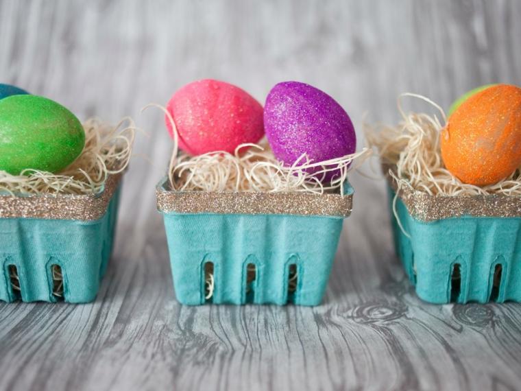 dei contenitori azzurri con il bordo argentato, della paglia bianca e delle uova pasqua dipinte di verde, viola, arancio e rosso
