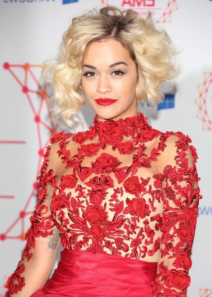capelli biondi mossi, vestito traforato con dei motivi floreali rossi, labbra rosse e occhi marroni