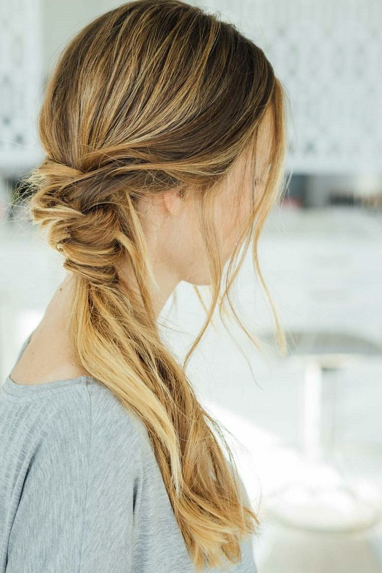 un'acconciatura raccolta per i capelli lunghi biondi e lisci e alcuni ciuffi sparsi