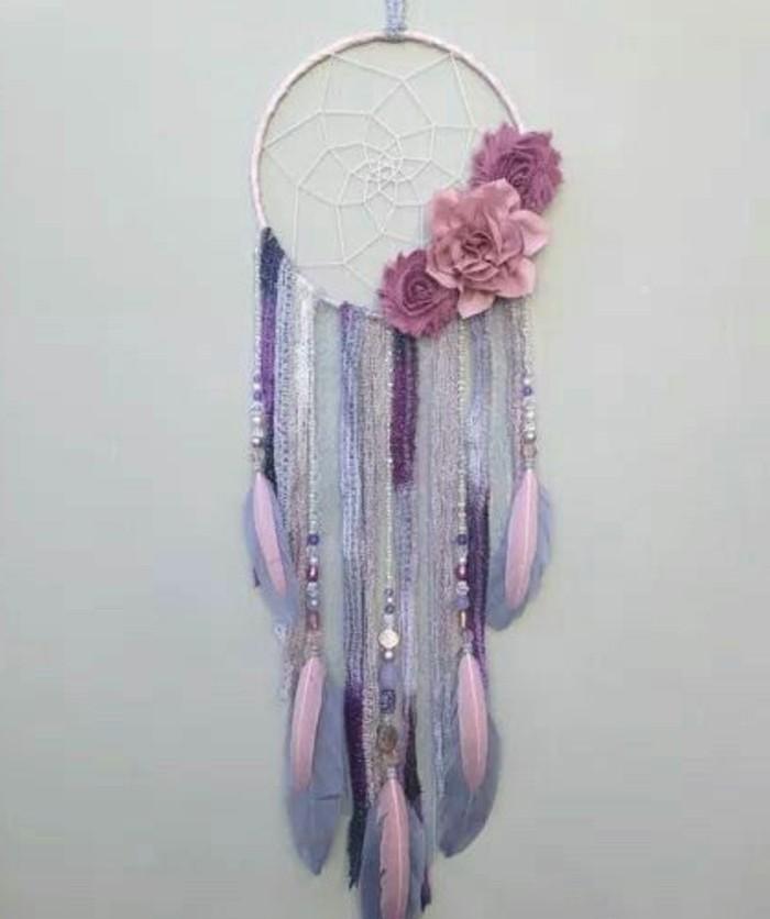 un modello di dream catcher nei toni del rosa e del viola con fiori e piume come decorazioni