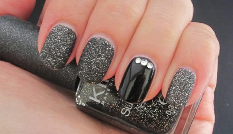 Unghie forma a mandorla con smalto grigio nero glitter, decorazione con tre brillantini