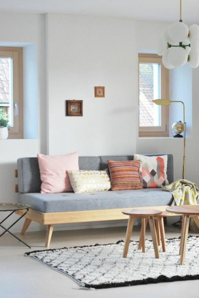 Salotto arredato con un divano piccolo e tavolini bassi, decorazione con un tappeto e cuscini
