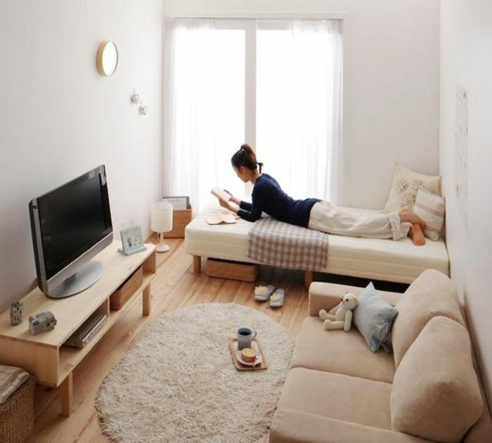 Camera da letto son un piccolo salotto arredato con divano beige e mobile tv basso in legno