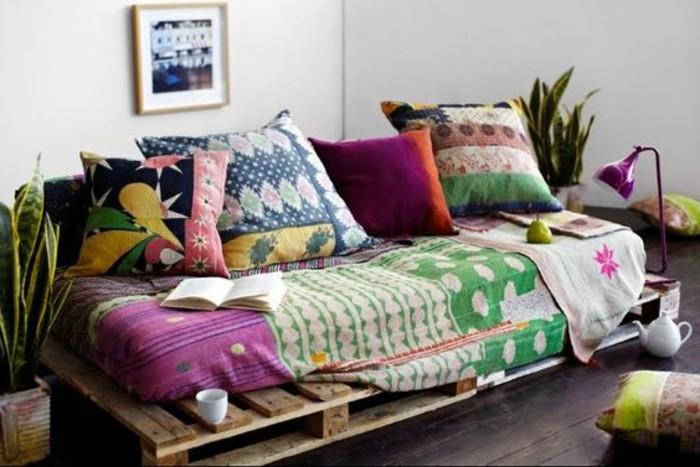 Idea divano pallet, aggiunta di materasso con motivi colorati, cuscini grandi sullo schienale