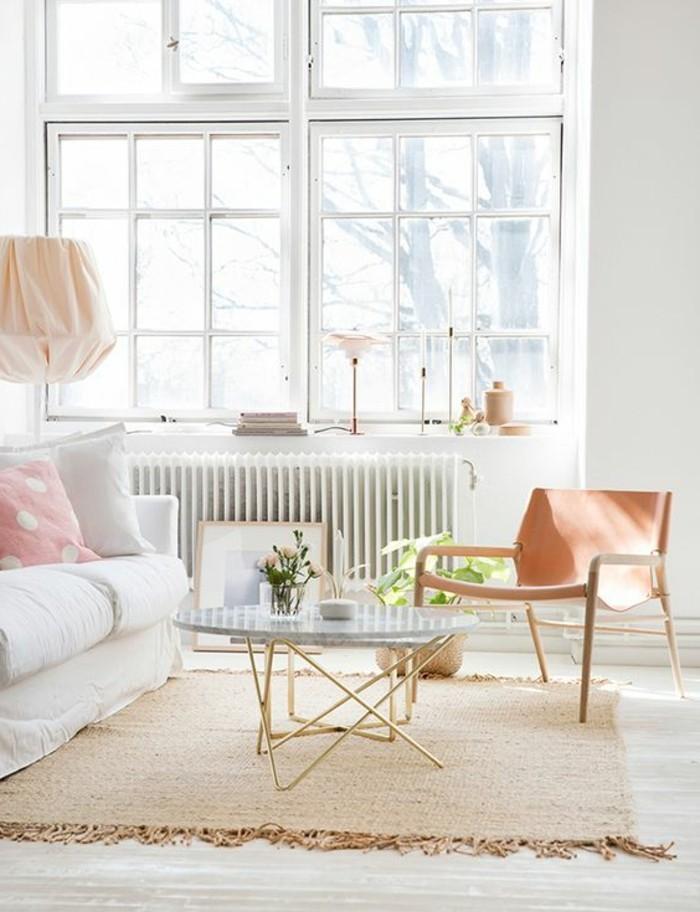 Zona giorno dalle dimensioni ridotte con un piccolo divano bianco e tavolino rotondo