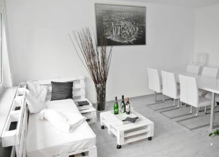 Open space arredato con un divano in pallet di colore bianco, tavolino basso con rotelle
