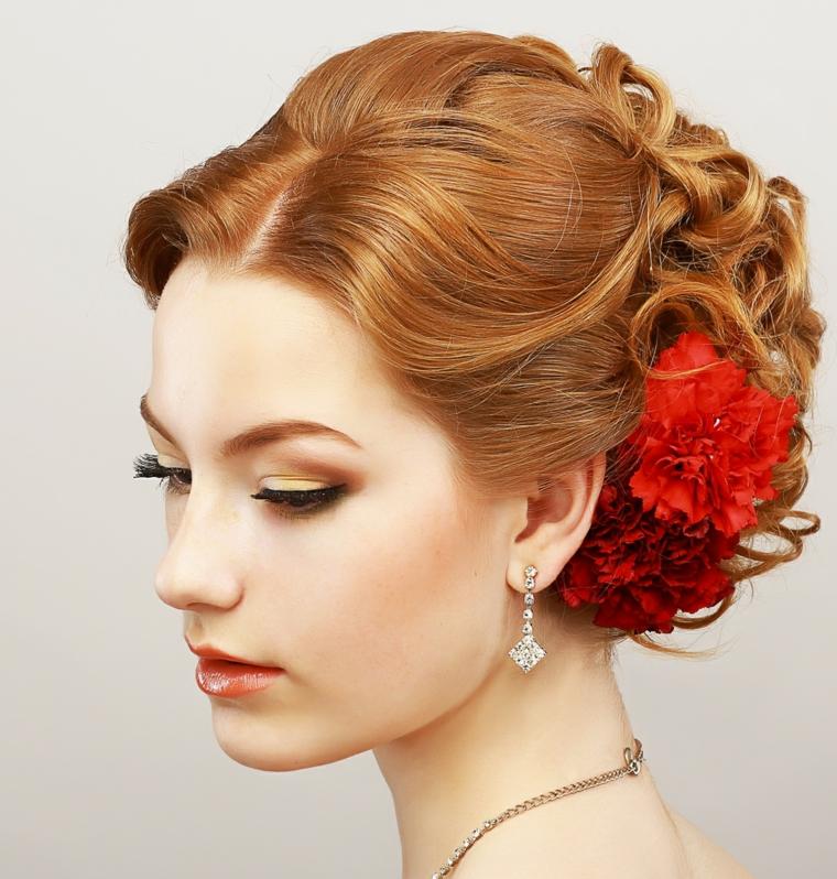 una ragazza con i capelli legati in un morbido chignon con dei fiori rossi, orecchini di brillanti e rossetto rosso