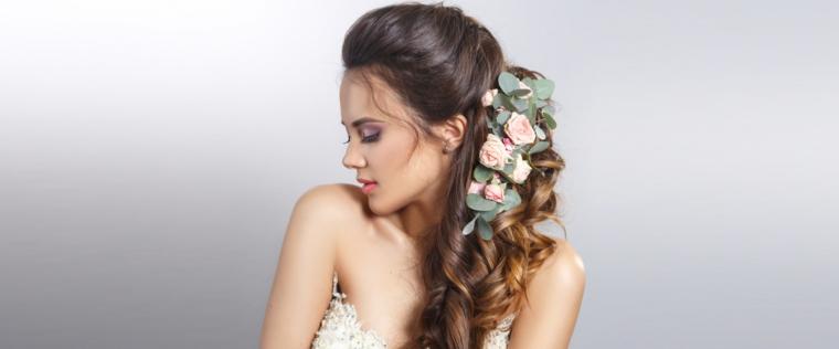 una ragazza con i capelli raccolti morbidi, ondulati e castani con delle rose e delle foglie