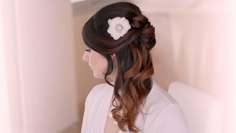 un esempio di capelli legati morbidi adatti ad una sposa con un grande fiore bianco a lato