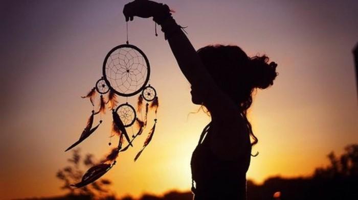 un tramonto dai colori sfumati, una ragazza di profilo con un mano un cattura sogni