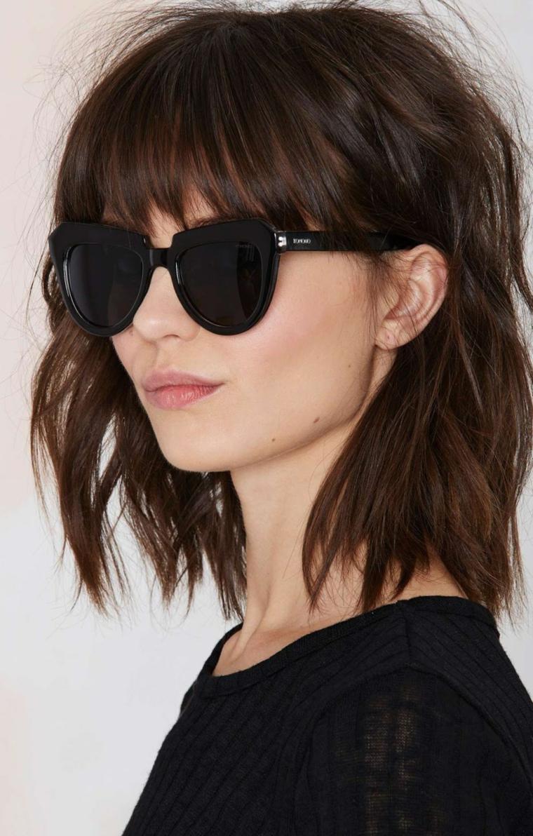 Taglio medio lungo per dei capelli castani con frangia, donna con occhiali stile cat eye