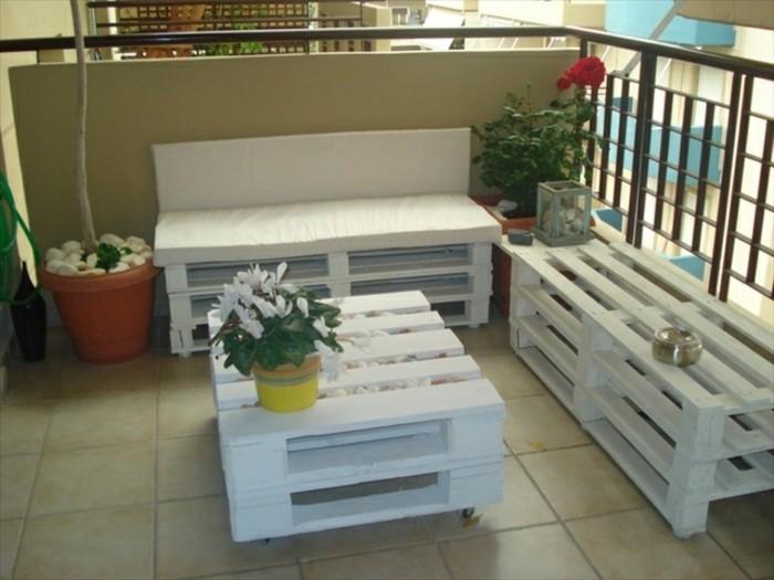 Balcone con ringhiera in ferro battuto, arredamento con bancali, divano e un tavolino