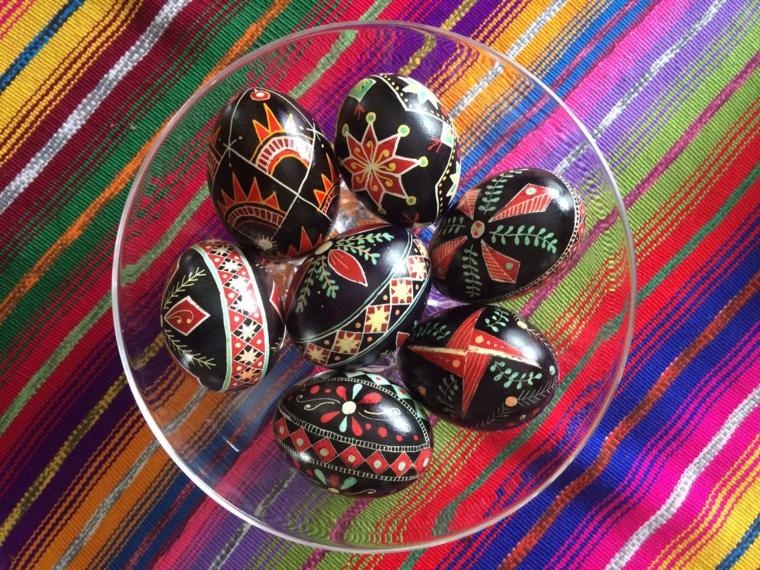 delle uova nere decorate con dei motivi rossi, bianchi, ora all'interno di una ciotola trasparente, come sfondo una tessuto multuicolore