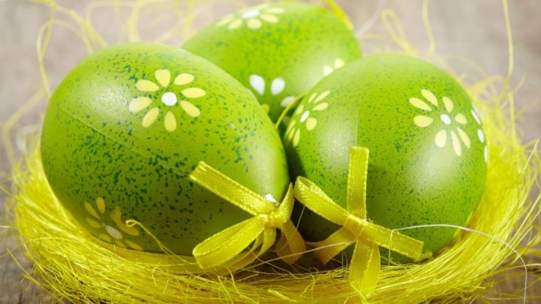 Uova di colore verde, decorazioni con fiorellini e fiocco verde, cestino paglia finta gialla