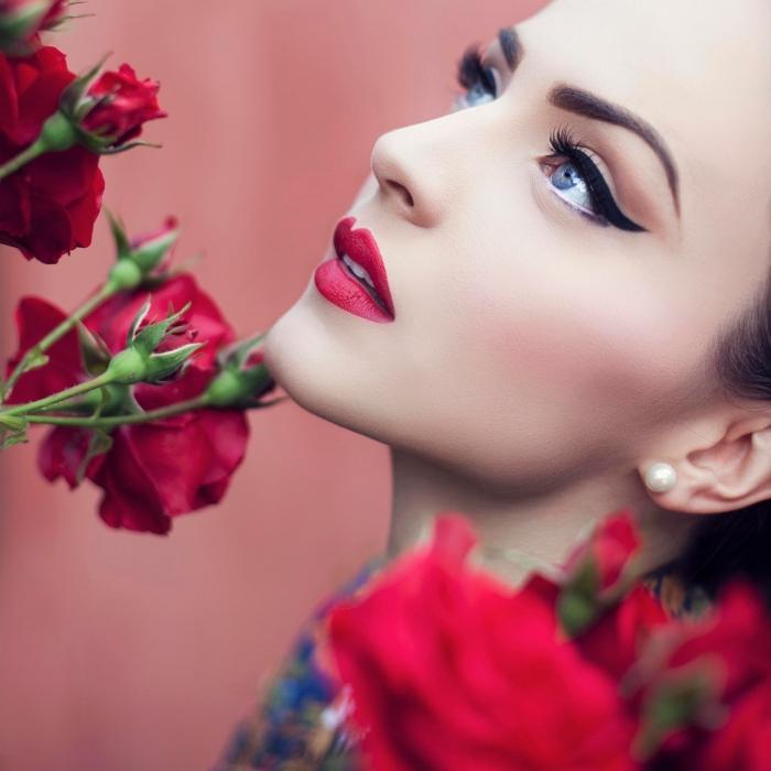 makeup rossetto rosso, occhi azzurri con eye liner nero, boccioli di rose rosse