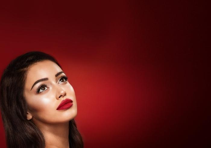 makeup novità con un rossetto rosso opaco, occhi castani e capelli lunghi castani