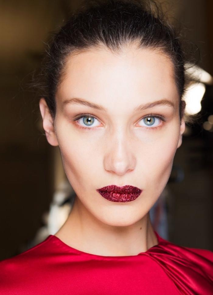 makeup nuove proposte con un rossetto rosso scuro, maglia rossa e occhi azzurri, capelli legati