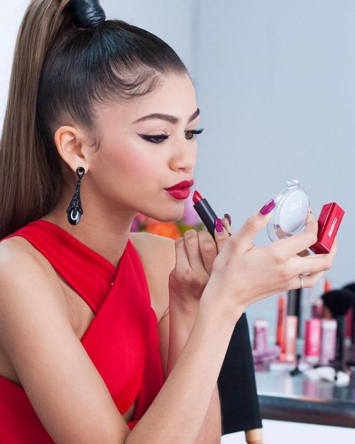 una proposta per un makeup novità con del rossetto rosso, un abito rosso intrecciato e la coda alta