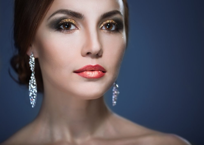makeup per la sera con dell'ombretto dorato, nero e argento, degli orecchini di brillanti