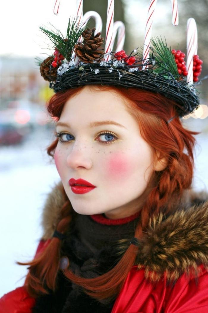 una ragazza con un makeup rossetto rosso, una ghirlanda natalizia come copricapo