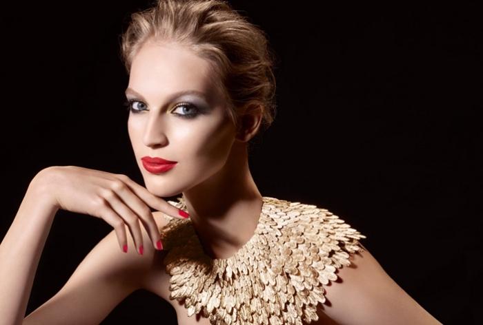 makeup per la sera con un rossetto rosso opaco, unghie rosse, occhi azzurri e capelli biondi
