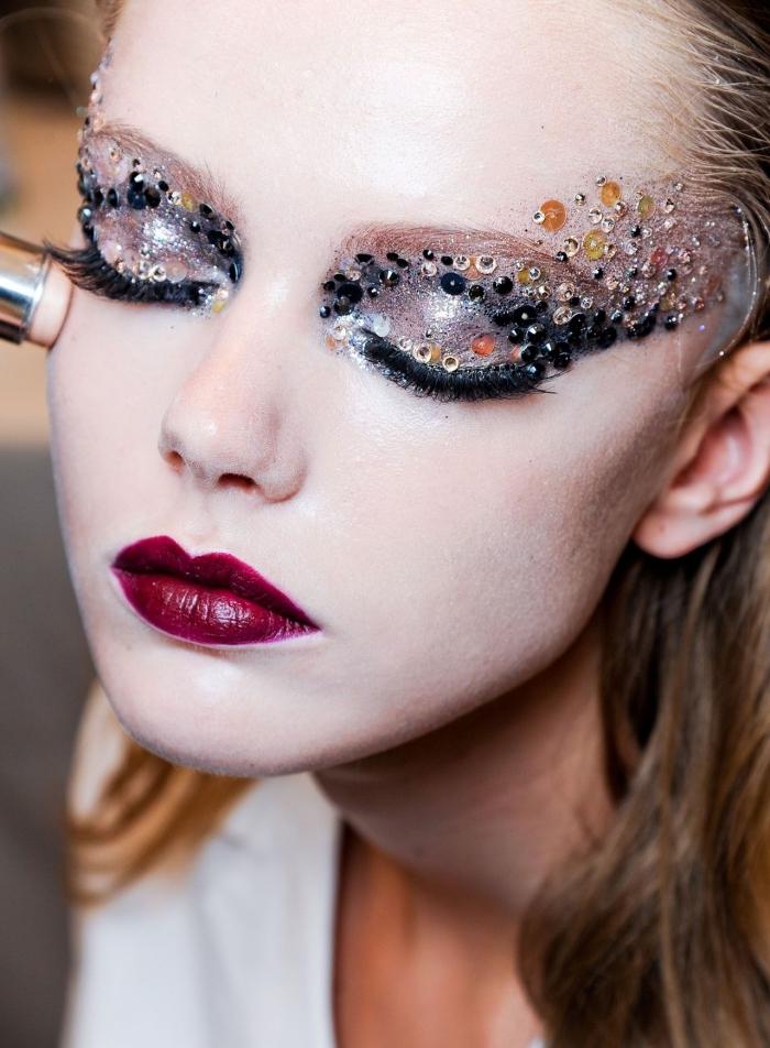 un makeup molto particolare con le labbra rosso scuro e gli occhi truccati con delle paillette e ciglia finte nere