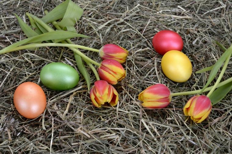 un'idea per come decorare le uova di pasqua colorandole in modo uniforme, della paglia e dei tulipani