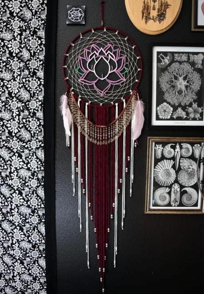 una proposta di acchiappa sogni di grandi dimensioni con un fiore all'interno del cerchio e due piume ai lati