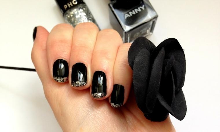 Mano donna con unghie bellissime di colore nero, french con glitter argento, rosa nera