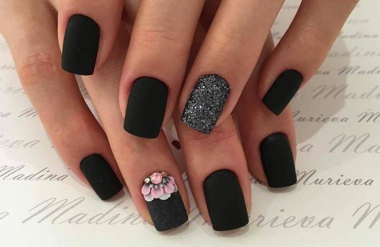 Unghie di colore nero mat, accent nail glitter argento, disegno fiori con piccoli brillantini