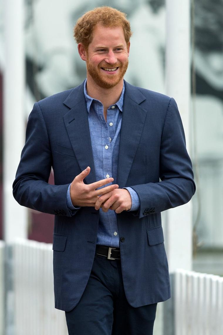 Il principe Harry che cammina, stile di abbigliamento casual, acconciatura capelli biondi uomo