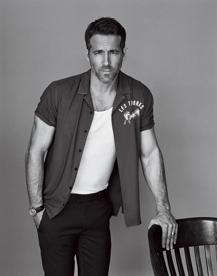 Ryan Reynolds appoggiato su una sedia di legno vestito in stile casual
