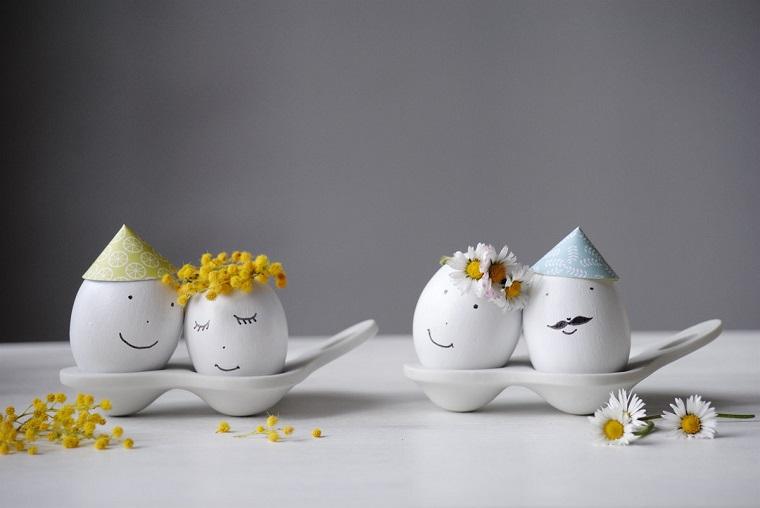 Dipingere le uova di bianco, faccine disegnate con pennarello nero, cappellini e fiori