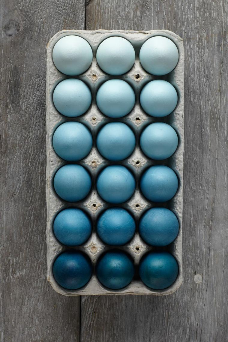 Colore blu in diverse sfumature, uova di Pasqua tinte, tavolo di legno rustico
