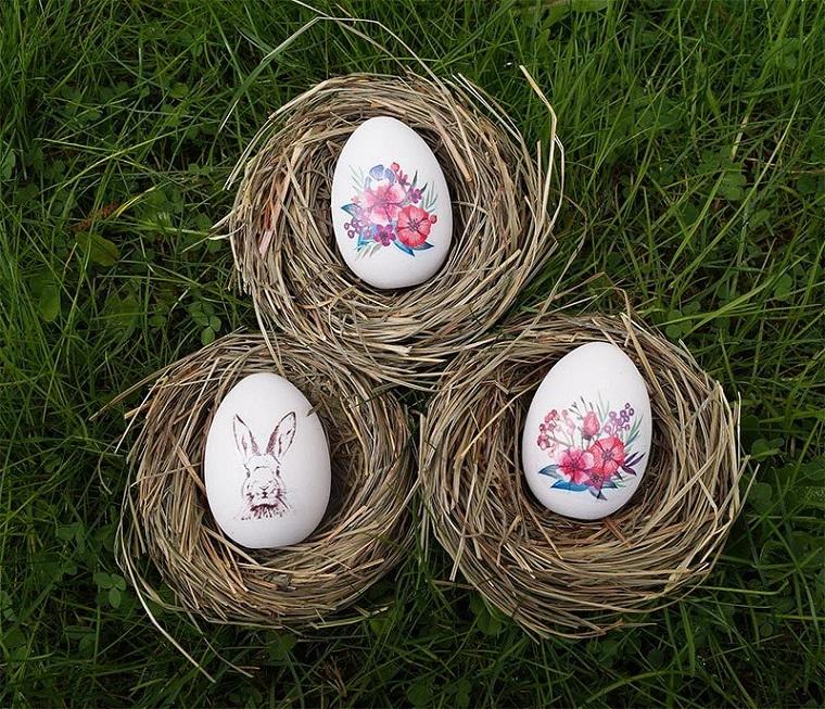 Lavori per pasqua fai da te, uova di colore bianco come base e decorati con stickers motivi floreali e coniglietti