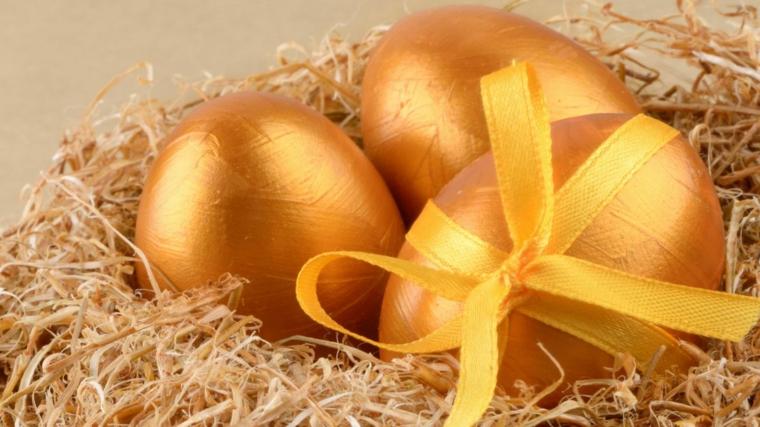 Colori a tempera e fiocco giallo, uova di Pasqua nella tonalità di colore oro