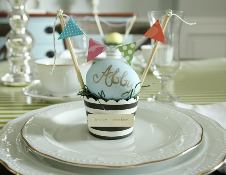 un'idea per realizzare un segnaposto con le uova colorate inserendolo in un cestino di carta con delle bandierine