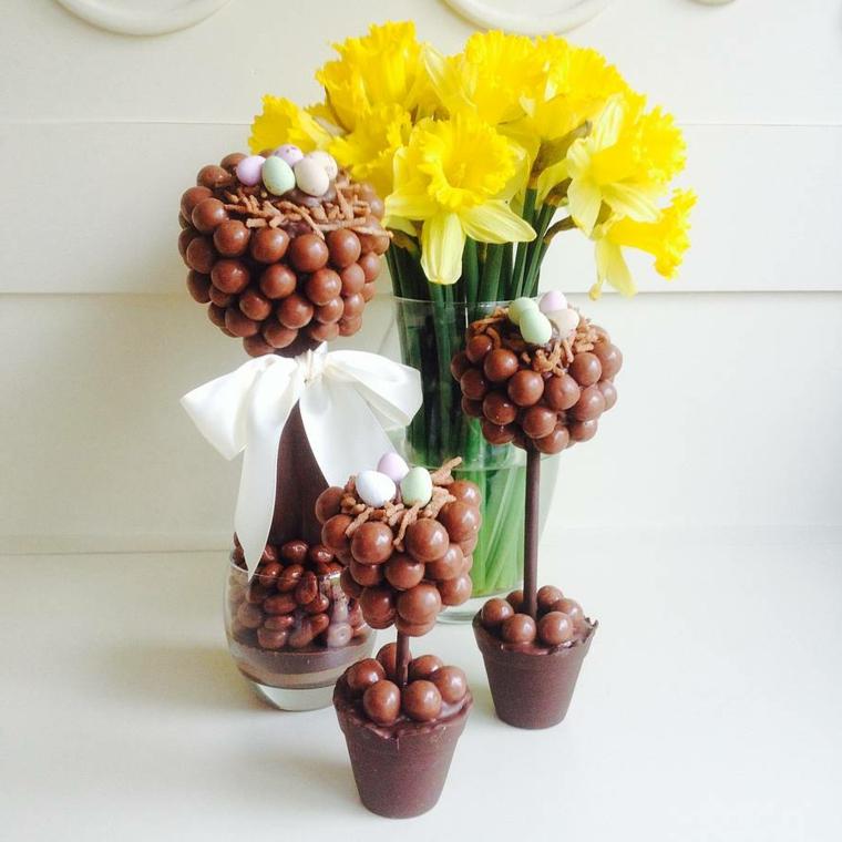degli alberi con delle uova di pasqua di cioccolata e un vaso con dei fiori gialli