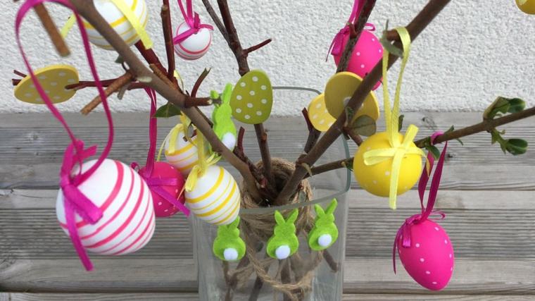 un'idea per degli addobbi di pasqua fai da te realizzato con dei rami e delle uova di polistirolo colorati