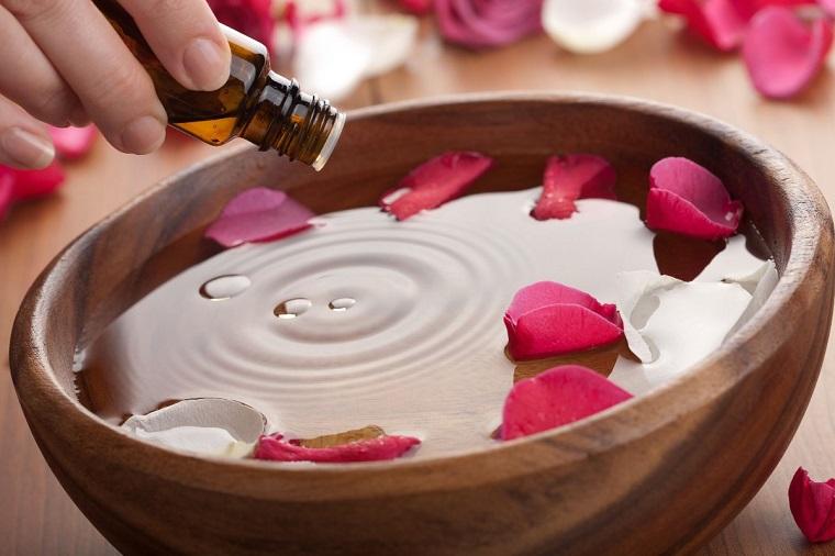 Metodo di cura basato su essenza vegetali, aromaterapia con olio di rosa, contenitore di legno con petali