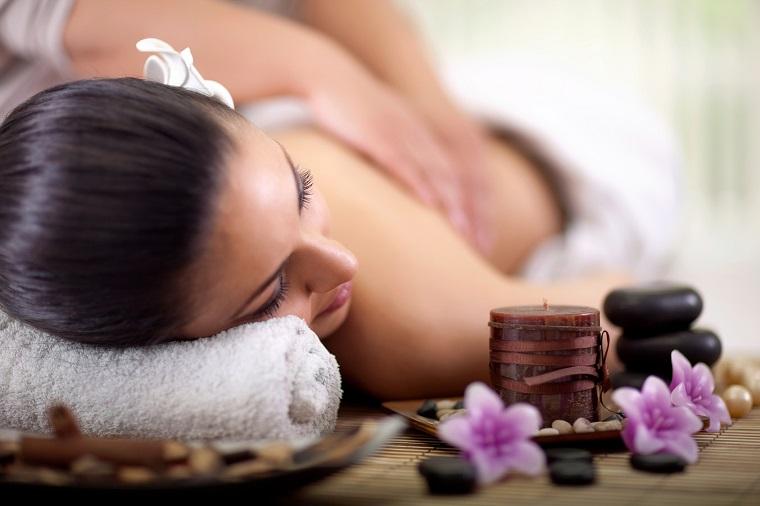 Donna con capelli neri che si fa massaggiare, fiori viola e sassi neri, olio eterico da massaggio