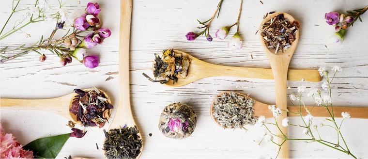 Petali di fiori e piante, oli essenziali bio per la cura del corpo, cucchiai di legno
