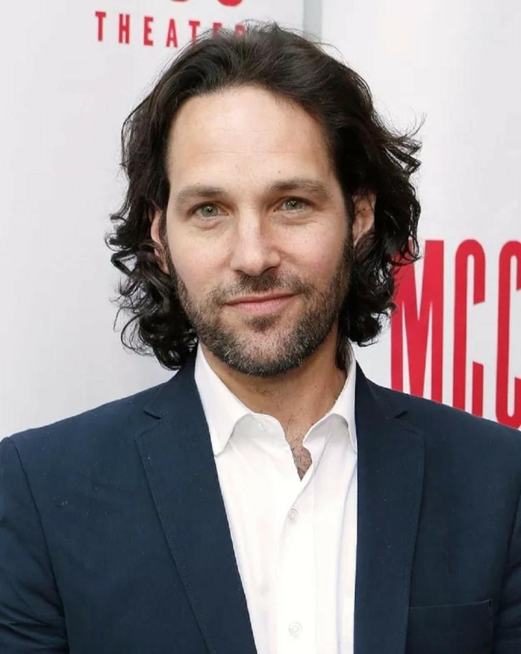 Uomo sorridente, acconciatura capelli lunghi di colore scuro, leggermente mossi