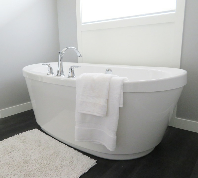 Piastrelle bagni moderni, vasca da bagno colore bianco, rubinetteria elegante color argento, pavimento colore nero